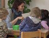 Kindergartenpädagogin mit Kindern am Tisch