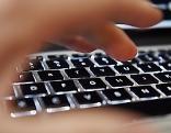 Mann tippt auf Computertastatur