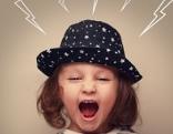 Kind mit Hut schreit, gezeichnete Blitze sind auf den Kopf gerichtet