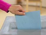 Hand mit Stimmzettel über Wahlurne