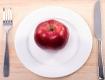 Auf einem Tisch auf einem weissen Teller liegt ein roter Apfel, links vom Teller eine Gabel, rechts vom Teller ein Messer