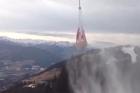 mit Schnee gefüllter Transportsack an einem Hubschrauber