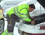 Pannenhelfer des ÖAMTC beugt sich im Winter über Motorraum eines Autos