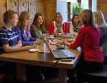 Frauen sitzen rund um einen Tisch