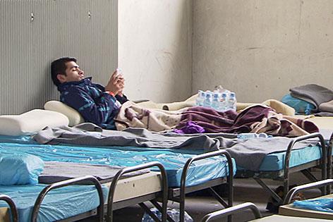 Asylwerber sitzt auf Bett in Notquartier