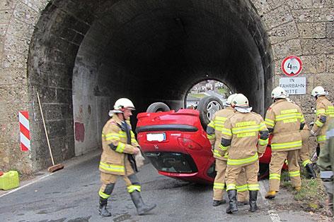 Unfallauto auf dem Dach vor Autobahnunterführung