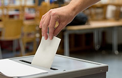 Ein Mann wirft einen Stimmzettel in eine Wahlurne