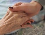Betreuerin hält Patientin die Hand