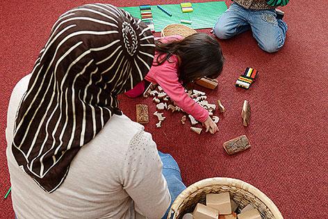Kindergärtnerin mit Kopftuch und Kind