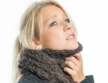 blonde frau mit dickem schal um den hals greift sich mit einer hand an den hals