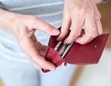 Person nimmt Scheine aus einer Geldbörse