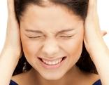 Frau hält sich die Ohren zu und verzerrt das Gesicht