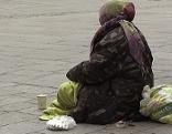 Bettlerin sitzt auf Straßenpflaster