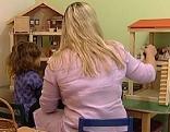 Psychologin und Kind bei Puppenhaus