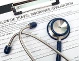 Stethoskop liegt auf einem Reiseversicherungsformular in einem Klemmbrett