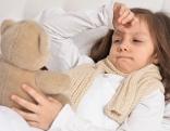 Krankes Kind liegt im Bett mit einem Teddybären