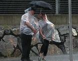 Pärchen mit Schirm im strömenden Regen eines Gewitters