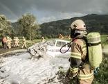 Abgestürztes Flugzeug mit Feuerwehrleuten