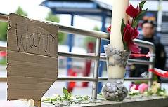 """Schild """"Warum?"""" und Blume vor dem abgesperrten Zugang zur U-Bahnstation Olympia-Einkaufszentrum in München"""