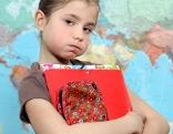 Junges Schulmädchen trägt eine Mappe und ein Federpenal vor sich und schaut genervt