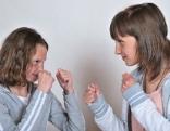 Zwei Schwestern stehen sich mit erhobenen Fäusten gegenüber