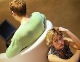 Mann sitzt auf Sessel mit dem Rücken zu einer Frau gedreht, die beleidigt am Boden sitzt