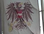 Fahne mit karikierten Bundesadlern mit Bananen auf Fahnenmast in Obertrum