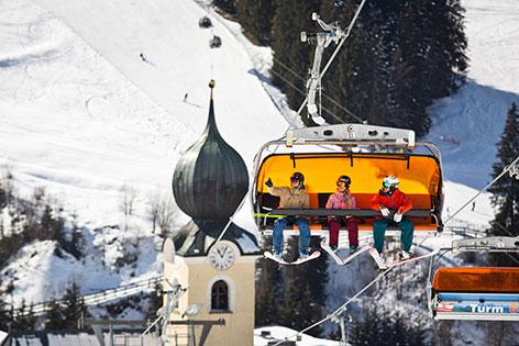 Skifahrer auf Sessellift vor Kirchturm