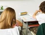 Lehrerin mit zwei Kindern bei Unterricht in Schule