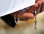 Priester hält Rosenkranz mit Kreuz