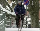 Radfahrer bei Schneefall auf Radweg
