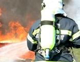 Feuerwehrmann löscht brennendes Auto