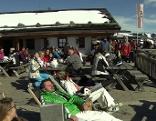 Gäste vor Skihütte beim Sonnenbad
