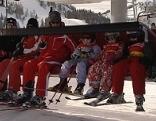 Sessellift mit automatisch öffnender Sicherung bei Bergstation mit Kindern und erwachsenen Skifahrern