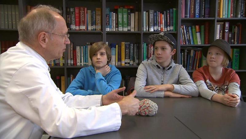 Werner Poewe mit drei Schülern