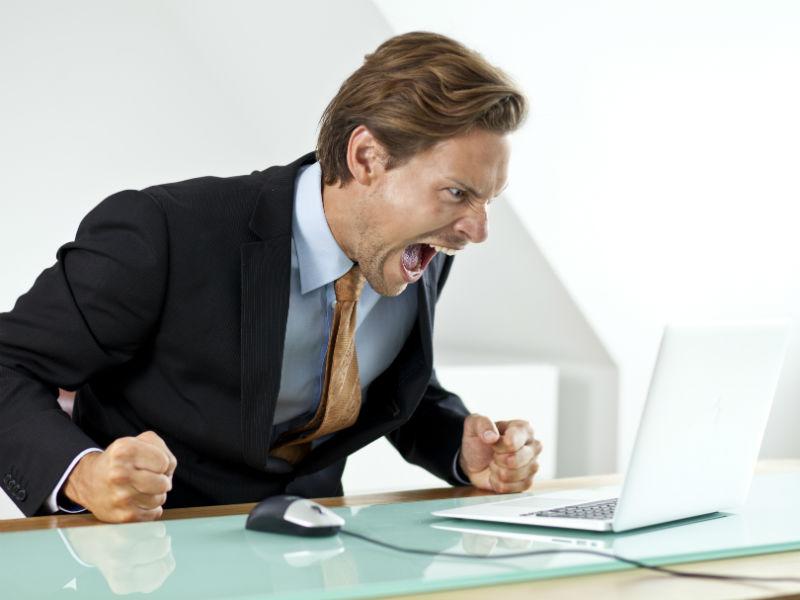 Wütender Geschäftsmann schreit seinen Laptop an
