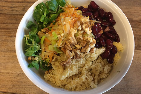 Buddha Bowl, eine Schale mit Gemüse, Couscous, Kidneybohnen, Nüssen und Dressing