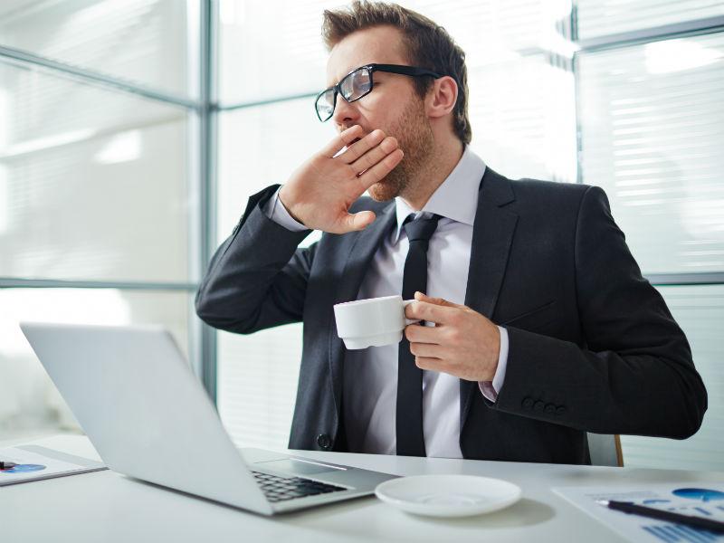 Geschäftsmann gähnt vor seinem Laptop