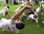 Capoeira Trainer mit Kindern bei Präsentation im Park