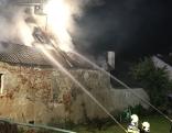 Feuerwehrmänner löschen den Brand eines Wirtschaftsgebäudes