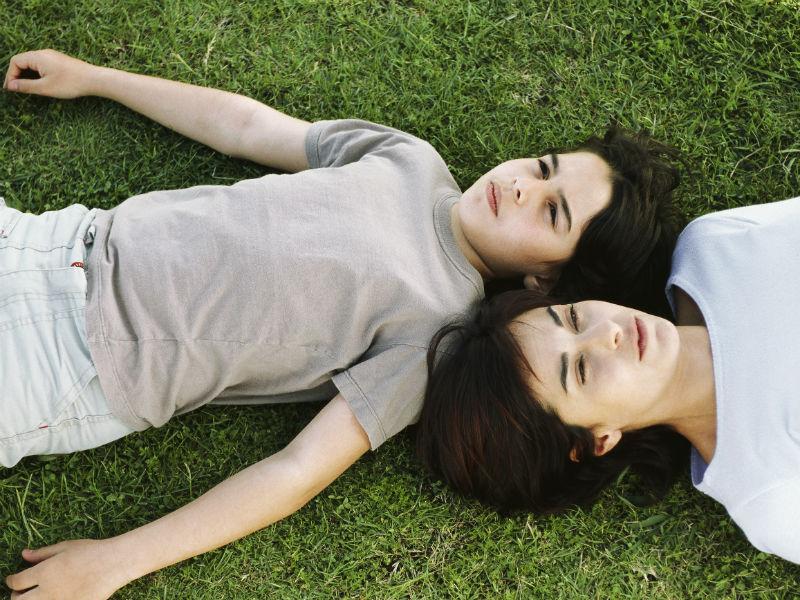 Mutter und Sohn liegen auf Gras und träumen