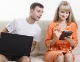 Mann und Frau sitzen mit Handy und Tablet auf Sofa