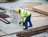 Arbeiter mit Helm und Schutzkleidung auf einer Baustelle