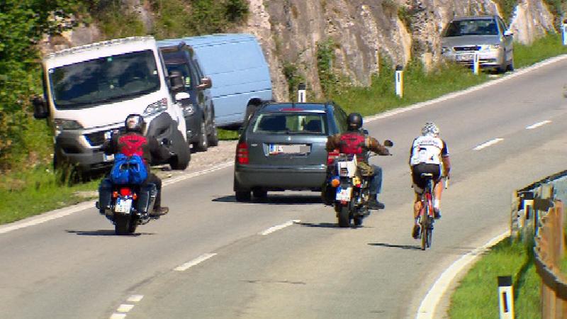 Auto und Motorräder überholen Rennradfahrer