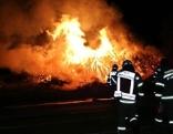 Feuerwehrleute löschen brennenden Holzstapel