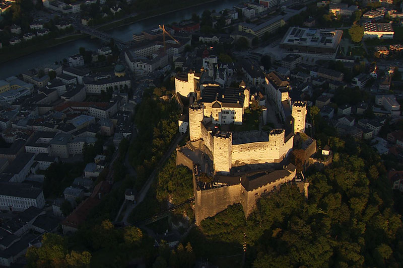 Festung Hohensalzburg und die Salzburger Altstadt im Abendlicht aus der Luft gesehen