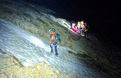 Bergretter bei nächtlichem Einsatz am Seil bei Schneefeld im Hochgebirge