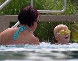 Mutter übt mit Kind schwimmen im Freibad