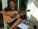 Musiker Manfred Kirchmeyer mit Gitarre auf dem sommerlichen Balkon
