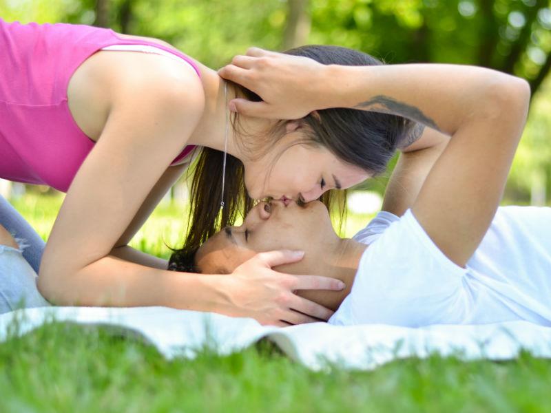 verliebtes Paar kuesst sich auf Wiese